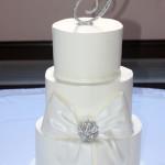 white buttercream cake with rhinestone monogram topper and rhinestone bow