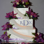 Purple orchids square monogram buttercream draping wedding cake