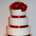 Red ribbon and tropical anthurium flower wedding cake